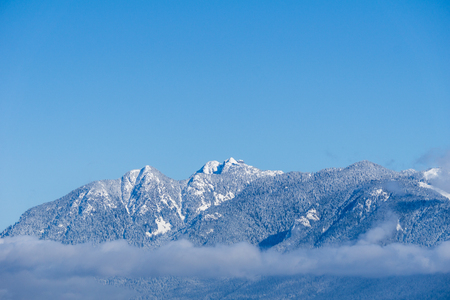 Mountains covered in snow and blue clear sky in nice winter day Stock Photo