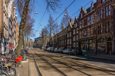 AMSTERDAM, NETHERLANDS - March 20, 2018 : narrow streets of Amsterdam at sunny spring day