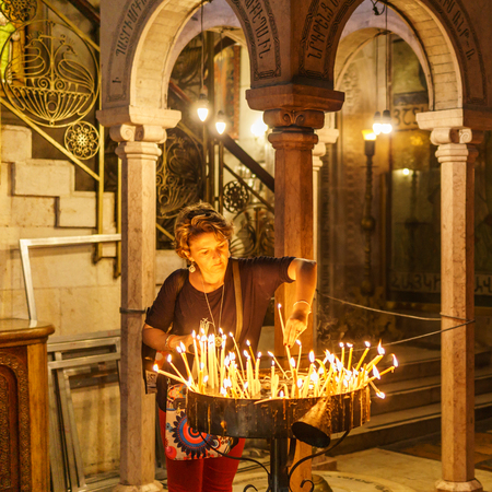JERUSALEM, ISRAEL - April 2, 2018: woman sets candles in the Church of the Holy Sepulchre
