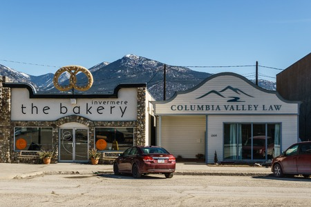 INVERMERE, CANADA - MARCH 21, 2019: main street in small town in British Columbia with shops restaurants cars.