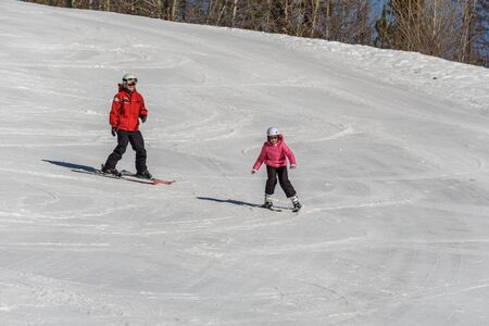 KIMBERLEY, CANADA - MARCH 22, 2019: Mountain Resort view early spring child and ski trainer skiing Sajtókép