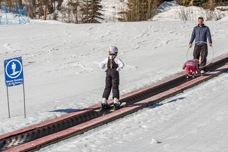 KIMBERLEY, CANADA - MARCH 22, 2019: people on magic carpet ski lift going uphill
