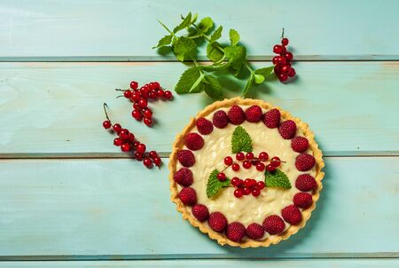 redcurrant pie with fresh berries as summer dessert on wooden background