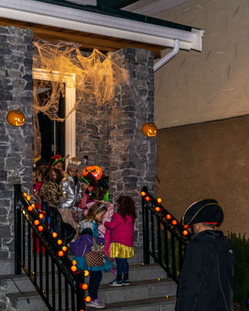 VANCOUVER, CANADA - October 31, 2019: Children in costumes knocking on door of decorated house trick or treat halloween night