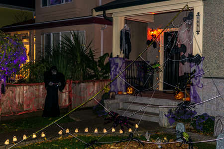 VANCOUVER, CANADA - October 31, 2019: Children in costumes knocking on door of decorated house trick or treat halloween night Editorial