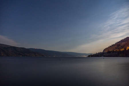starry sky seen from the shore of Okanagan lake at night with city of Penticton Canada 免版税图像