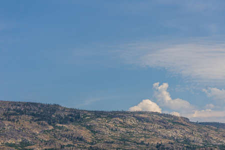 Sky with white clouds above small mountains in okanagan valley Canada. 免版税图像