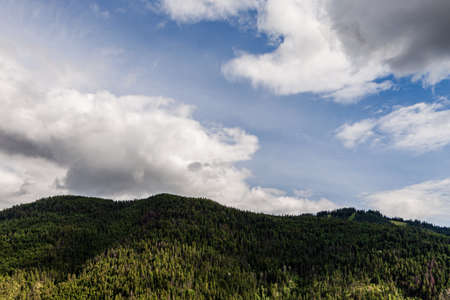 Sky with white clouds above small mountains in british columbia Canada.