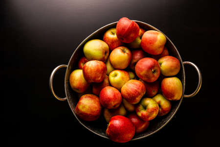 Ripe red apples in washtub on dark background top view