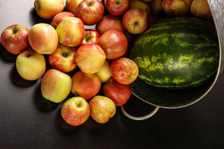 Ripe red apples and watermelon in washtub on dark background top view 免版税图像