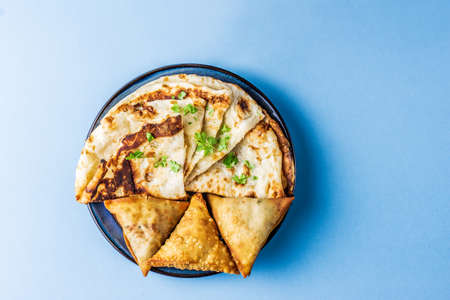 Indian snacks samosa garlic naan bread on wooden table 免版税图像