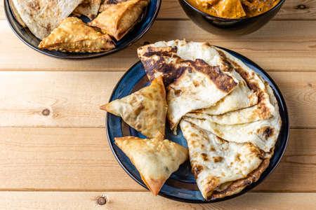 Indian snacks samosa garlic naan bread butter chicken on wooden table