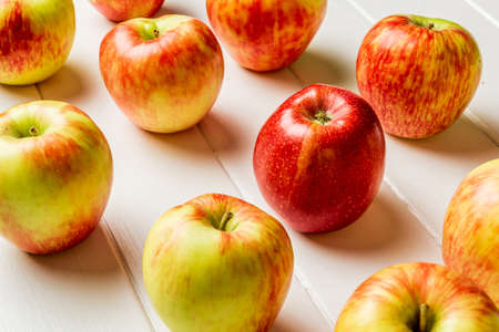Fresh apples on a white wooden background.