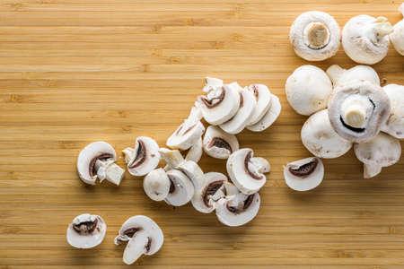 Fresh mushrooms champignon on a wooden board.