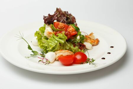 Greek salad with a sea food on a white plate