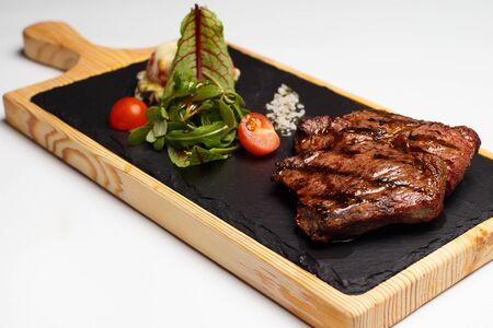 beef rib eye with a salad on a wood