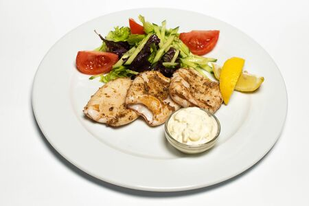 grilled squid with tartar sauce and vegetables on a white plate Stockfoto