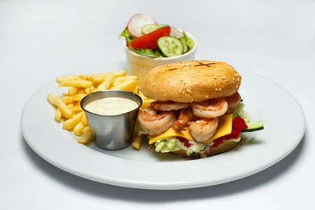 shrimp burger with caviar, vegetable salad and french fries, shrimp sauce on a white background Stockfoto