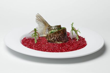 fish with red bean garnish on a white plate