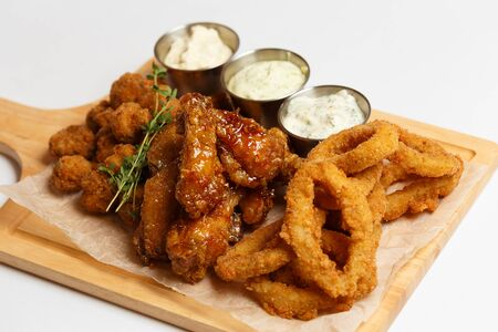 grilled wings, deep-fried squid rings, appetizers with sauces