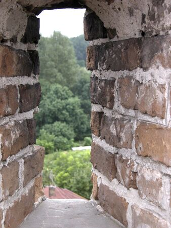 embrasure: Green live trees. View from narrow window of castle wall. Loophole, embrasure