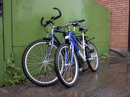 Two bicycles at green gate and brick wall