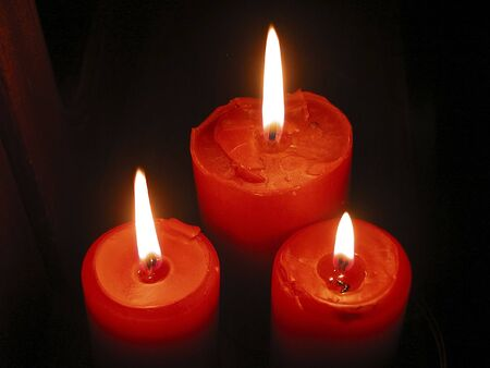 Three burning red candles on black background photo