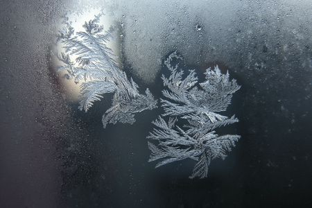 Silver frost drawings on transparent window glass photo