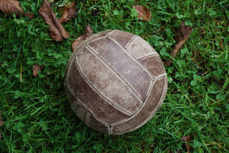 Old brown volleyball ball on green grass