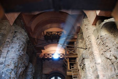 The beam of sunlight under cupola of old tower restored with ancient walls