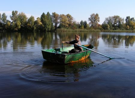 Boy in small boat with oars on still river water Stock Photo - 835487