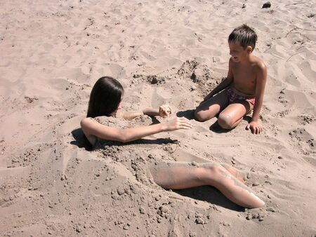 Boy and girl playing on sand beach photo