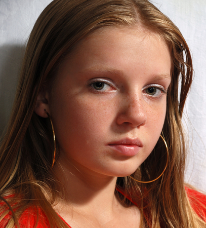 freckled: Portrait of young long-haired model with big ear-rings Stock Photo