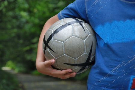 Boy with football bal in blue T-shirt
