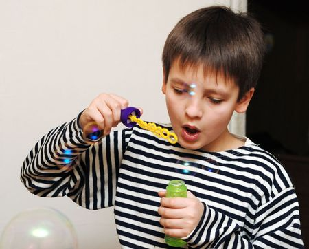 full face: Boy in striped vest blows soap bubbles intently, full face