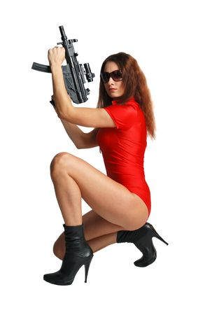Model in red catsuit squats and takes up a tommy-gun, isolated, white background