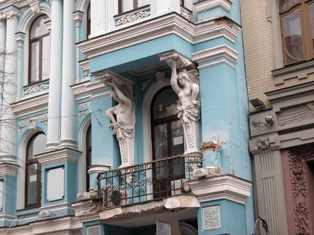 caryatids: Two white cariatids ornated balcony of ancient blue mansion, Kiev Stock Photo