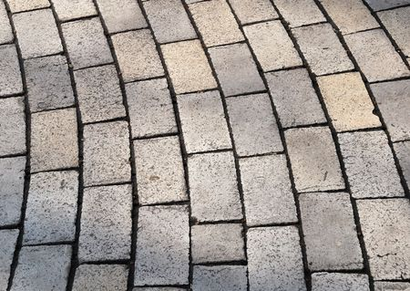 scabrous: Bent cobble pavement rows, scabrous pale surface and black edges of every cobbles Stock Photo