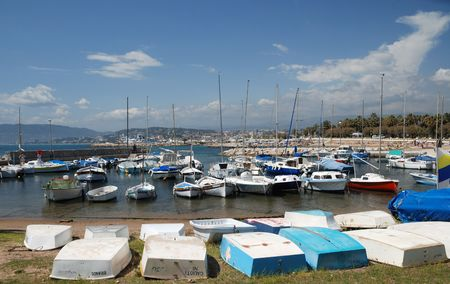 Harbour with a lot of vessels near Nice against blue cloudy sky, cutters upturned ashore in the foreground photo