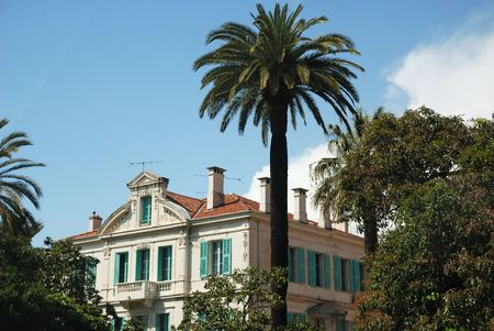 Mediterranean mansion with blue shutters in the middle of green trees and lofty palms, blue cloudy sky, France Stock Photo - 3049667
