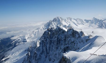 White steep peaks of the Alps against blue sky and snow slope with mountain-skiers, Mont Blanc, France; steel rope in the foreground photo