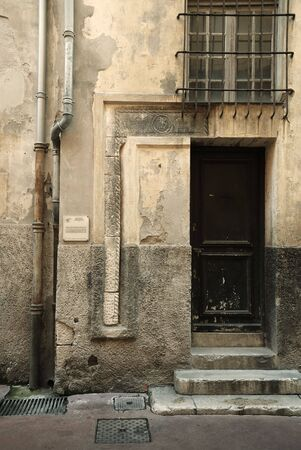 Ancient walls with close door and bars on window, some stone footsteps, Nice, France Stock Photo - 3076960