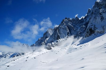 Steep peaks in light clouds and snow slopes against blue sky, the Alps, Mont Blanc, France photo