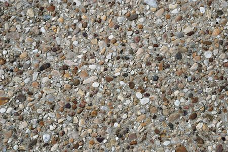 Multicoloured background of pebbles and various stones in river grey sand photo