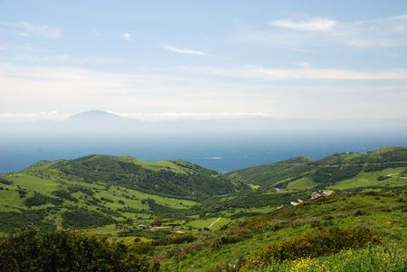 Green hills of Tarifa against the azure sea, hazy mountains in the background, view from above photo