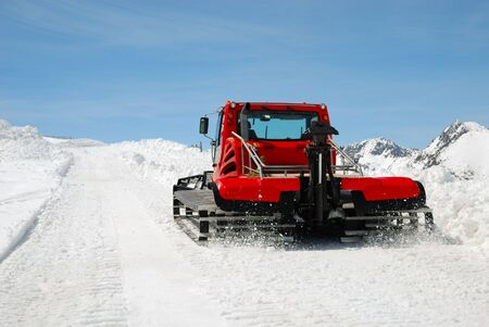Red catterpillar tractor makes snow slope against blue sky on Pyrenees pass photo