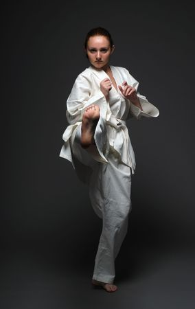 jiu jitsu: Girl in white uniform throws forward right leg, the dark background
