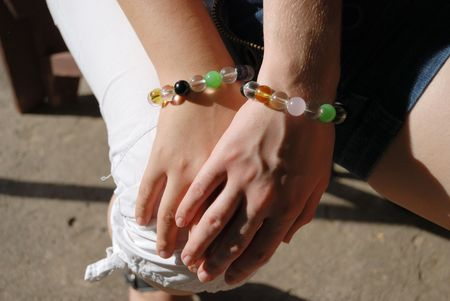 Girlish hand covered with another maidenly hand in equal bracelets against legs in white trousers and short skirt photo