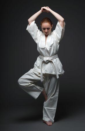 頭、暗い背景の上に結合した手で 1 本の足に立っている白い制服を着た少女 写真素材