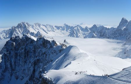 Snow slope with mountain-skiers against blue sky and steep peaks of the Alps, Mont Blanc, France Stock Photo - 3439386